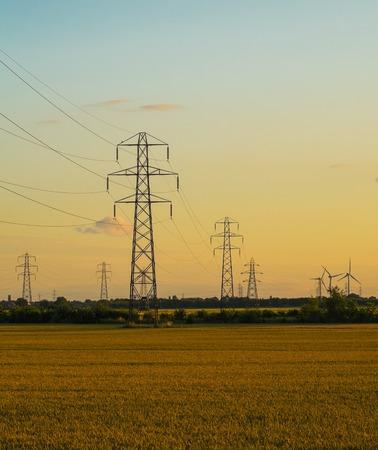 torres el�ctricas: torres de alta tensi�n de campo ina en la tarde Foto de archivo