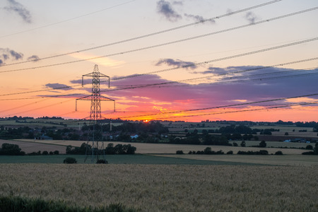 sunset shot of electricity pylon in field with multiple power lines Stock Photo