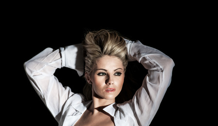 pretty blonde woman with arms behind her head on black background