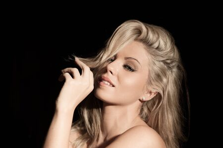 portrait of pretty blonde woman on black background