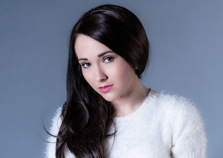 beautiful dark haired woman in white sweater on blue background Stock Photo