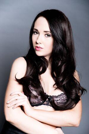 beautiful dark haired woman posing in bra on grey background