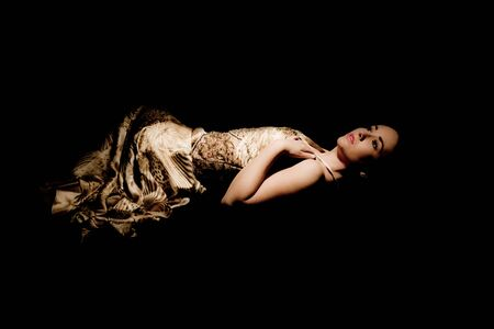 brunette woman in evening gown lying down on black background Stock Photo