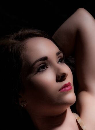 low key portrait of beautiful dark haired woman on black background