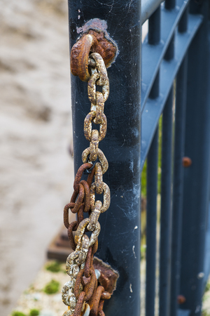 close up of rusted chain attached to metal fence