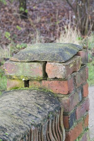end of a weathered brick wall showing cracks and missing mortar