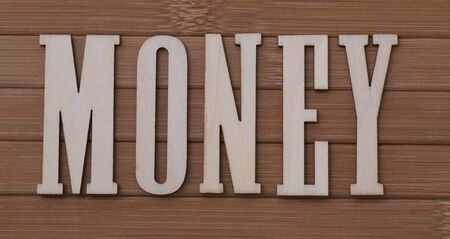 wooden letters spelling the word money on bamboo background Stock Photo