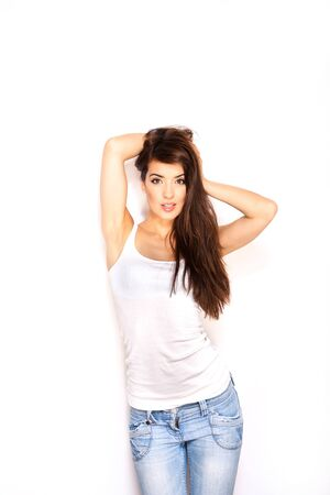 attractive woman in white vest and jeans on white background