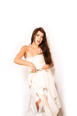 attractive brunette using scissors to cut up her wedding dress Stock Photo