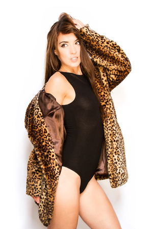 attractive brunette posing in leotard and leopard skin coat