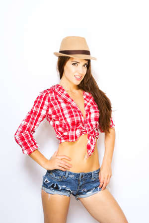 attractive woman in tied shirt, shorts and hat
