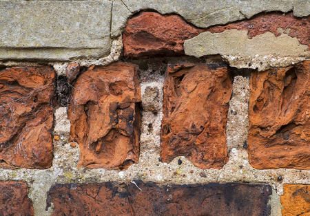 close up of badly weathered bricks with some repairs