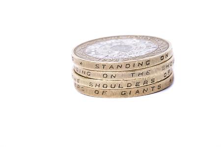 巨人の肩に立っているモットーを示す英国の 2 ポンド硬貨のスタック