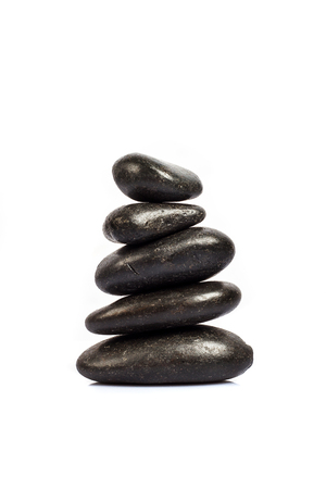 stack of five black stones on a white background Stock Photo