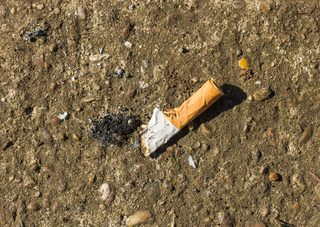 stubbed out cigarette butt on a concrete background Stock Photo