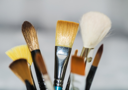 Various artists paint brushes of different sizes and shapes