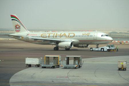 towing: ABU DHABI, UAE - MARCH 10, 2015: Towing aircraft Airbus A320-232 A6-EIR Etihad Airways in passenger terminal Abu Dhabi Airport Editorial