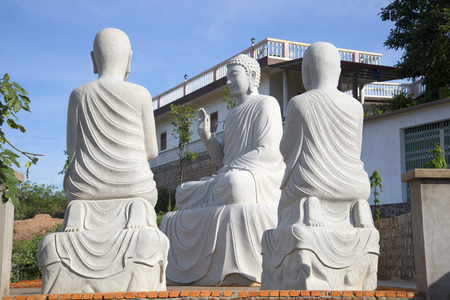 disciples: Buddha with two disciples. Sculptural composition at a Buddhist temple. Phan Thiet. Vietnam