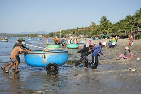 december 25: MUI NE, VIETNAM - DECEMBER 25, 2015: Fishermen pull a plastic boat from the sea. The fishing harbor. Mui Ne