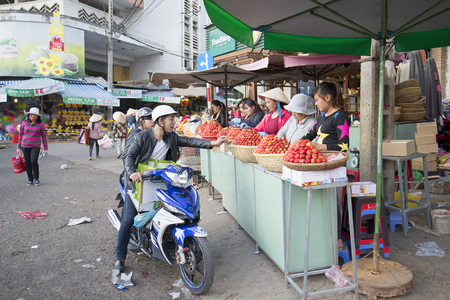 dalat: DALAT, VIETNAM - DECEMBER 26, 2015: A man on a motorcycle buys strawberries in the central market of Dalat