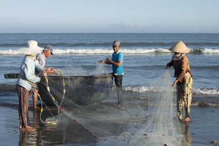 dismantle: DA NANG, VIETNAM - JANUARY 04, 2016: Fishermen dismantle the network before going out to sea