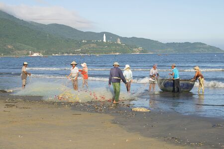 dismantle: DA NANG, VIETNAM - JANUARY 04, 2016: A group of fishermen dismantle the network before going fishing