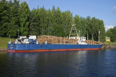 loaded: SAIMAA CANAL, FINLAND - AUGUST 09, 2015: Russian ship STK-1004 loaded with timber stands in the customs area of ??the Saimaa canal