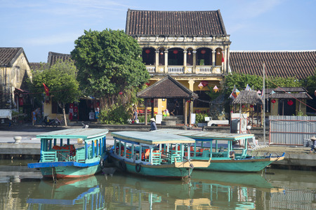 hoi an: HOI AN, VIETNAM - JANUARY 04, 2016: Three tourist boats on the backdrop of ancient Chinese houses Editorial