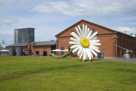 turku: TURKU, FINLAND - JUNE 13, 2015: Giant daisy flower on background of the building of the exhibition center Forum Marinum Editorial