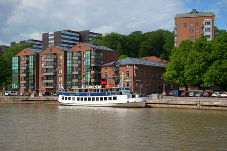 turku: TURKU, FINLAND - JUNE 13, 2015: The modern embankment of the river Aura on a summer day. Tourist boat moored to the pier in Turku, Finland