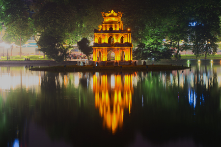 returned: Ancient Temple of Turtles on the background of the waterfront Hoan Kiem lake in the night illumination. Hanoi, Vietnam Stock Photo