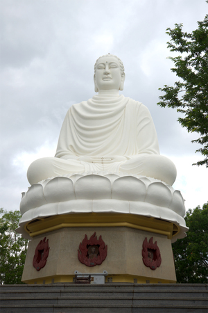 sean: Giant statue of Buddha sitting in the pagoda Long Sean, cloudy day. Nha Trang, Vietnam Stock Photo