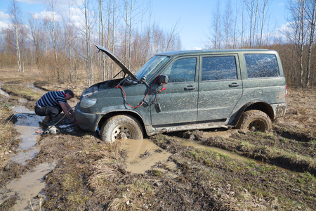 pull out: LENINGRAD REGION, RUSSIA - APRIL 16, 2016: The driver installs electric winch to pull out of the mud UAZ-Patriot Editorial