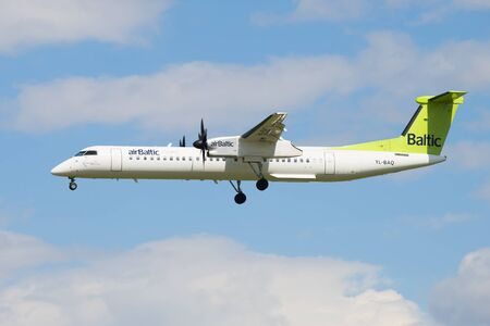 bombardier: SAINT PETERSBURG, RUSSIA - MAY 17, 2016: Aircraft Bombardier DHC-8-402 NG (YL-BAQ) airline airBaltic in the cloudy sky