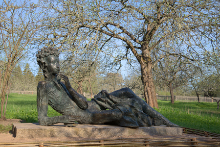 gory: Sculpture Pushkin-Lyceum student in an Apple orchard, may morning. Mikhailovskoye, Pushkinskie Gory, Russia