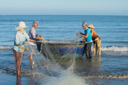 untangle: DA NANG, VIETNAM - JANUARY 04, 2016: Fishermen untangle a network, ready to go to sea for fishing