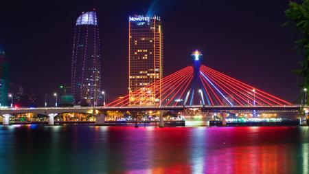 DA NANG, VIETNAM - JANUARY 06, 2016: The South bridge on the background of the modern Novotel Danang Premier Han River. Night in Da Nang, Vietnam