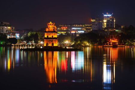 HANOI, VIETNAM - DECEMBER 13, 2015: Turtle Tower and the Ngoc son temple on the background of night citys waterfront. The lake of the Returned sword, the historical center of Hanoi Editorial