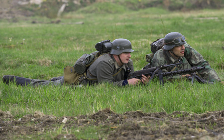 episode: SAINT PETERSBURG, RUSSIA - MAY 05, 2015: German infantryman and machine gunner lay down in the grass. Reconstruction of the episode of the great Patriotic war