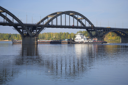 River tugboat with barges passes under the road bridge. Rybinsk