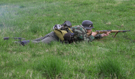 LENINGRAD REGION, RUSSIA - MAY 05, 2015: German infantryman lies in the grass. Reconstruction of the episode of the great Patriotic war Editorial