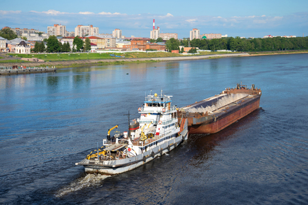 RYBINSK, RUSSIA - JULY 10, 2016: River towboat Alexander Lagutin with a barge up the river Volga Editorial