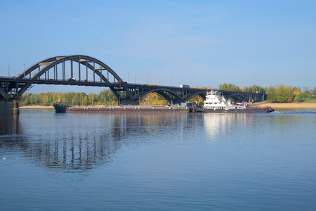 RYBINSK, RUSSIA - SEPTEMBER 26, 2015: River tug OT-2078 with a barge passes the bridge on the river Volga Editorial