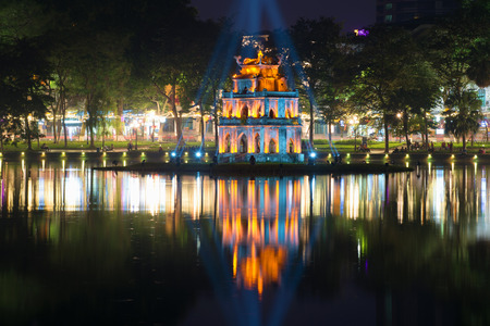 HANOI, VIETNAM - JANUARY 10, 2016: A tower of the Turtle against the background of the city embankment in a night landscape. Hanoi, Vietnam