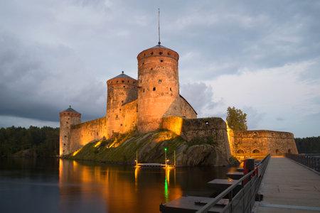 SAVONLINNA, FINLAND - AUGUST 20, 2016: Olavinlinns fortress in August twilight in night illumination. Savonlinna, Finland