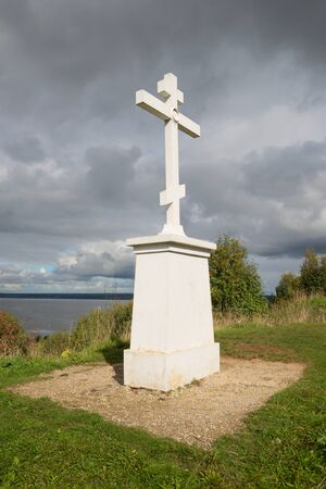 memorial cross: GALICH, RUSSIA - SEPTEMBER, 2016: Memorial cross in memory of the dead inhabitants of Galicia in the time of Troubles (1609) on the mountain-red cloud September day. Galich, Russia