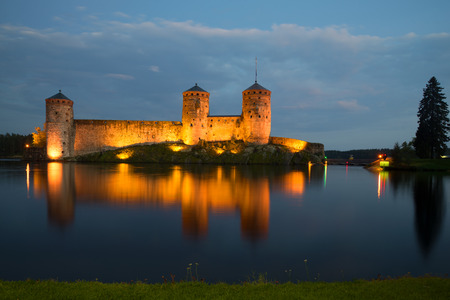 Old fortress of Olavinlinna on the Saimaa lake in night illumination in the August evening. Savonlinna, Finland Stock Photo