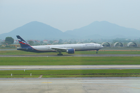 HANOI, VIETNAM - JANUARY 12, 2016: Contact point. The Russian Boeing 777-3M0 (VP-BGC) of the Aeroflot company makes landing at the airport of Noybay. Hanoi, Vietnam