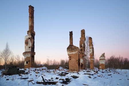 Heating furnaces on the ashes of the burned-down two-storeyed house in the January evening. Working village Russian America. Leningrad region, Russia