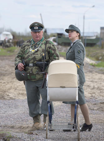 SAINT PETERSBURG, RUSSIA - MAY 05, 2015: The man in the form of the field gendarmerie and the girl in the uniform of a German with a pram. Reconstruction of the episode of the great Patriotic war Editorial